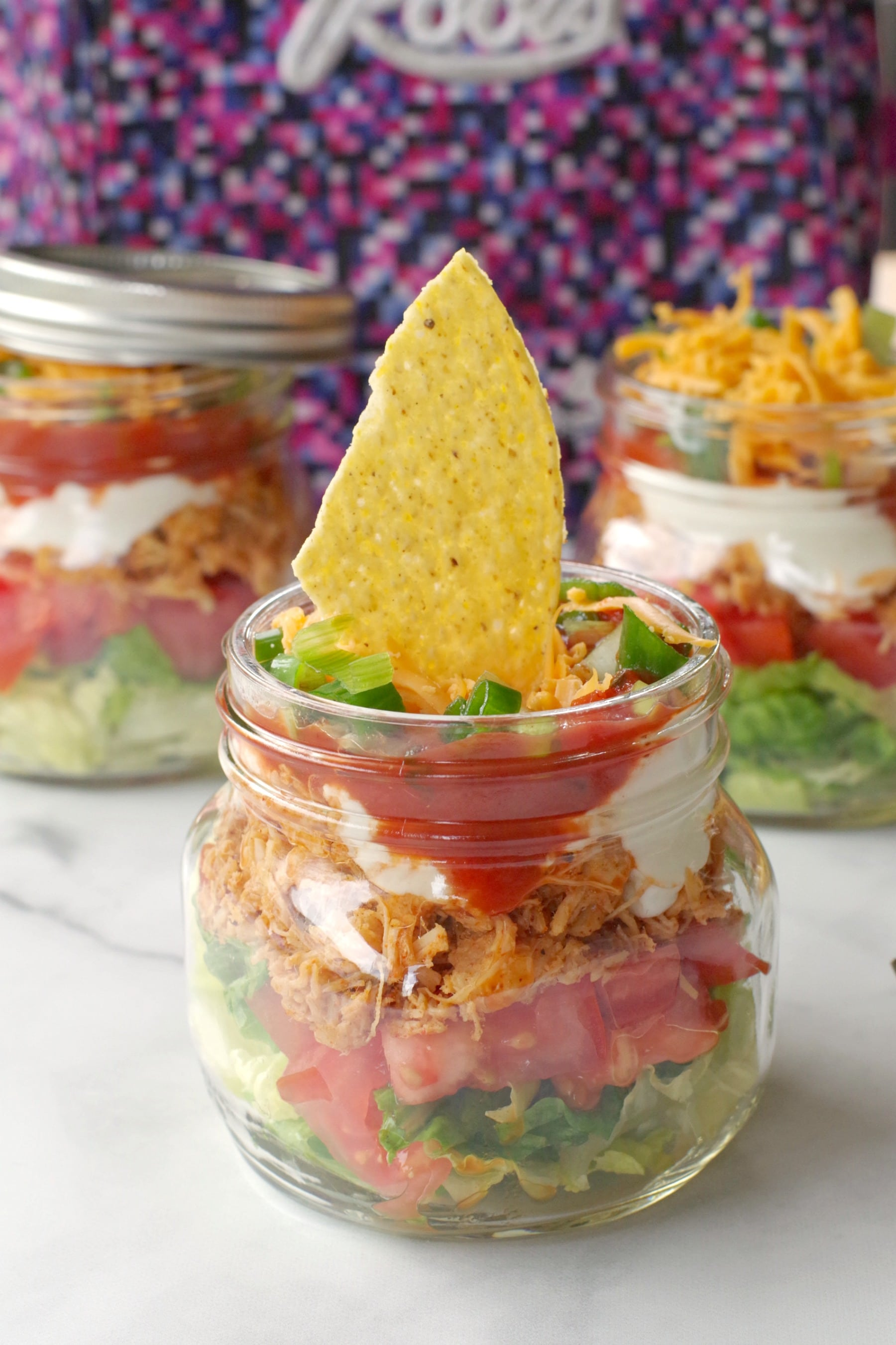 mason jar taco salad with more jars and lunchbag in background