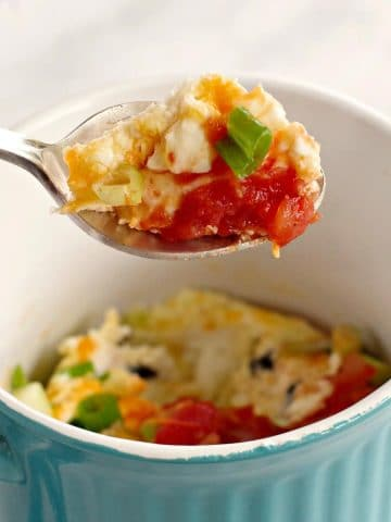 microwave mug omelette being held up on spoon over blue mug