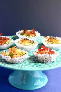 Muffin tin sushi cups on blue platter