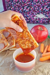 pizza dipper being dipped into pizza sauce with pieces, an apple, carrots and lunch bag in background.