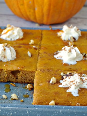 pumpkin spice pancakes on a sheet pan with one pancake missing and pumpkin in background