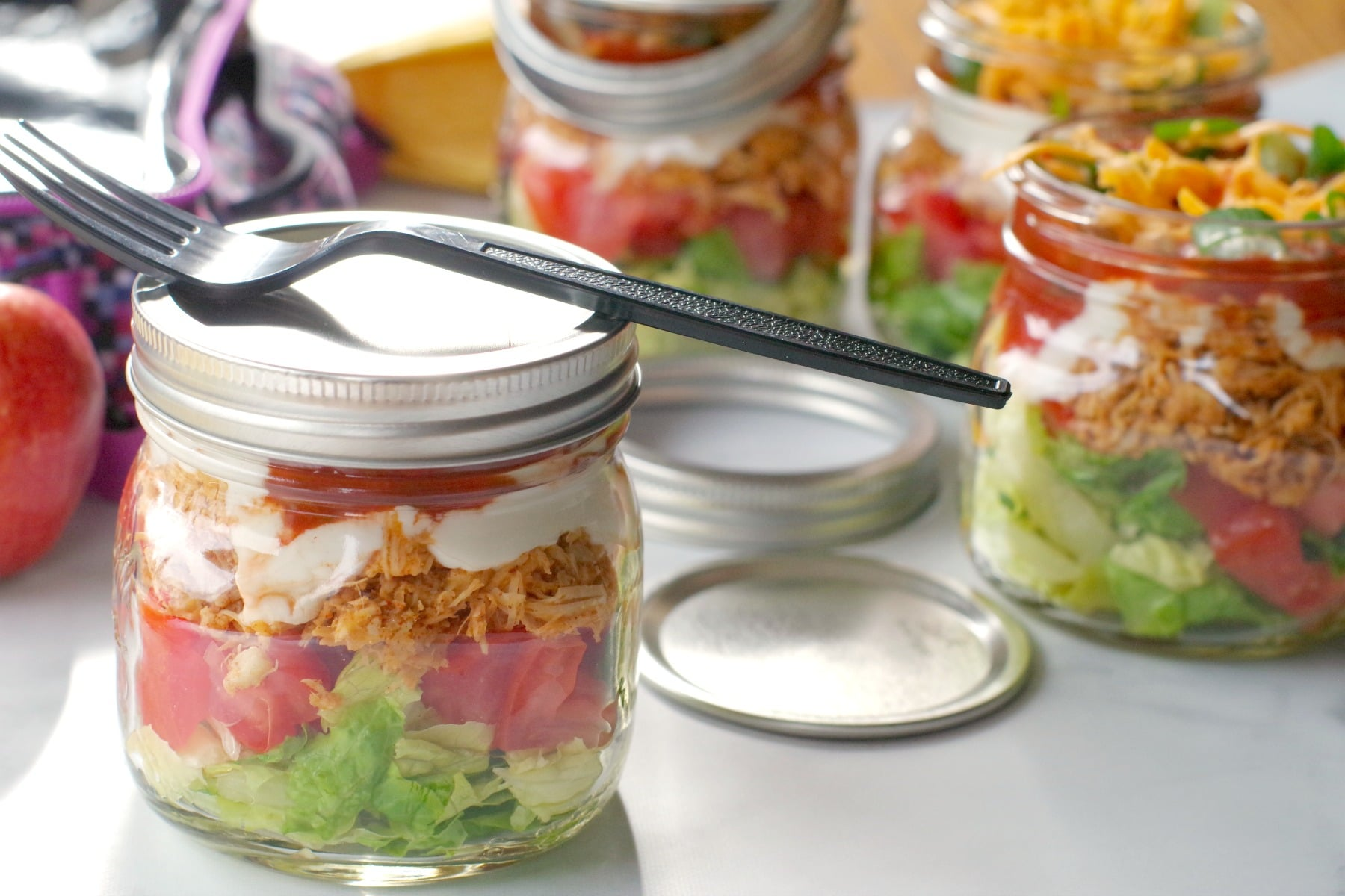 chicken taco salad in a mason jar with lid on and more jars in background