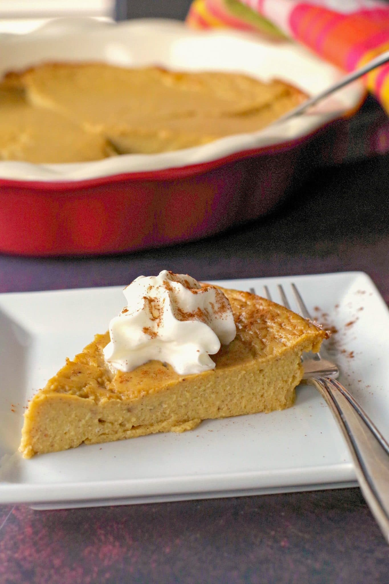 WW no crust pumpkin pie on a white plate with fork and whole pie in background