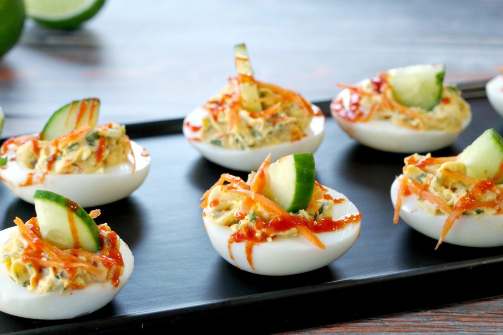 banh mi devilled eggs on a narrow black serving platter