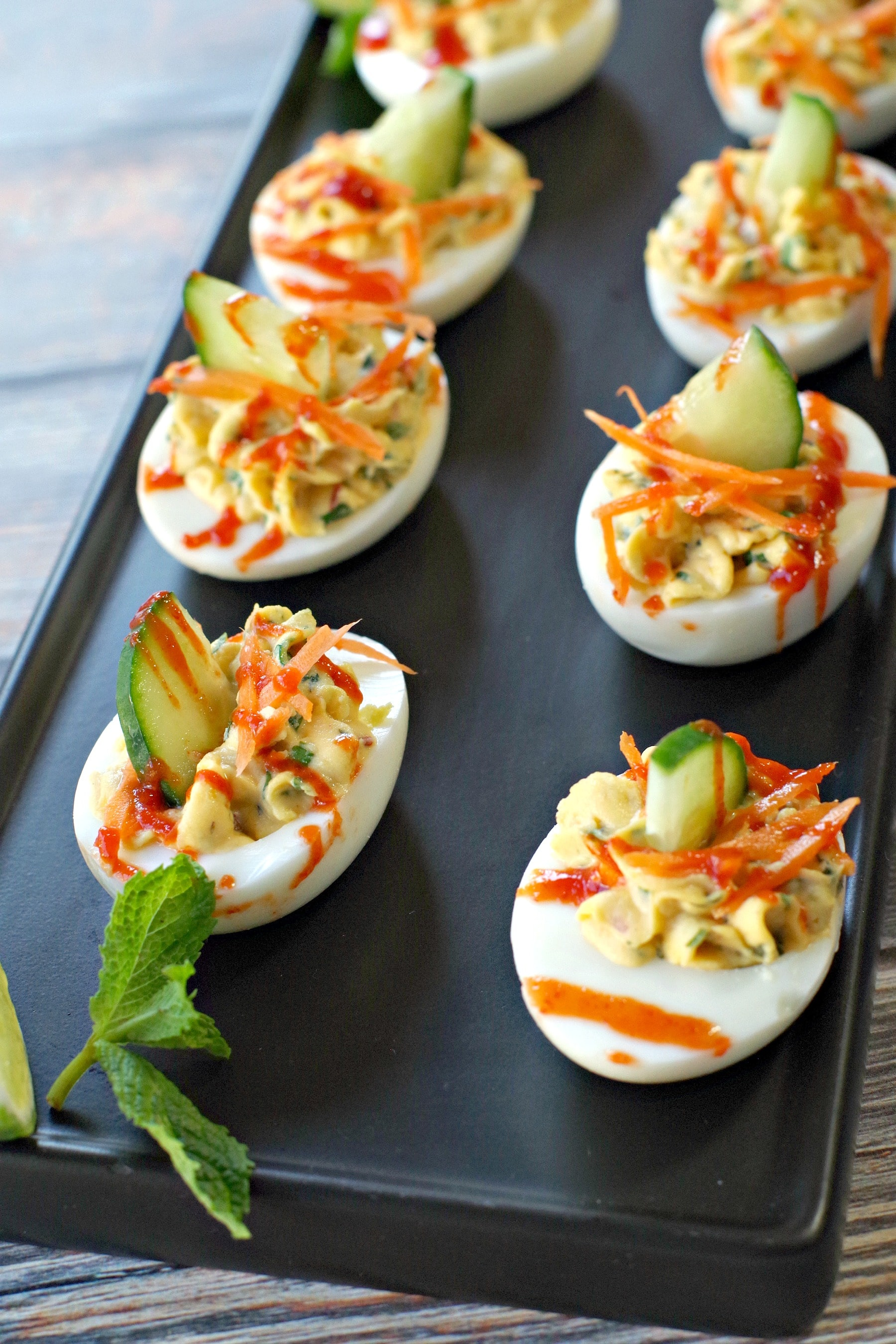 banh mi devilled eggs on a black tray with mint garnish