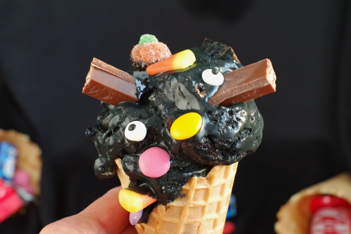 Boo batter ice cream in a cone being held in a hand