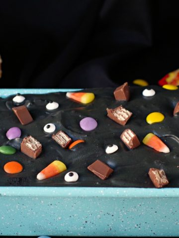 Halloween Boo Batter in a blue speckled loaf pan with candy and cones in the background