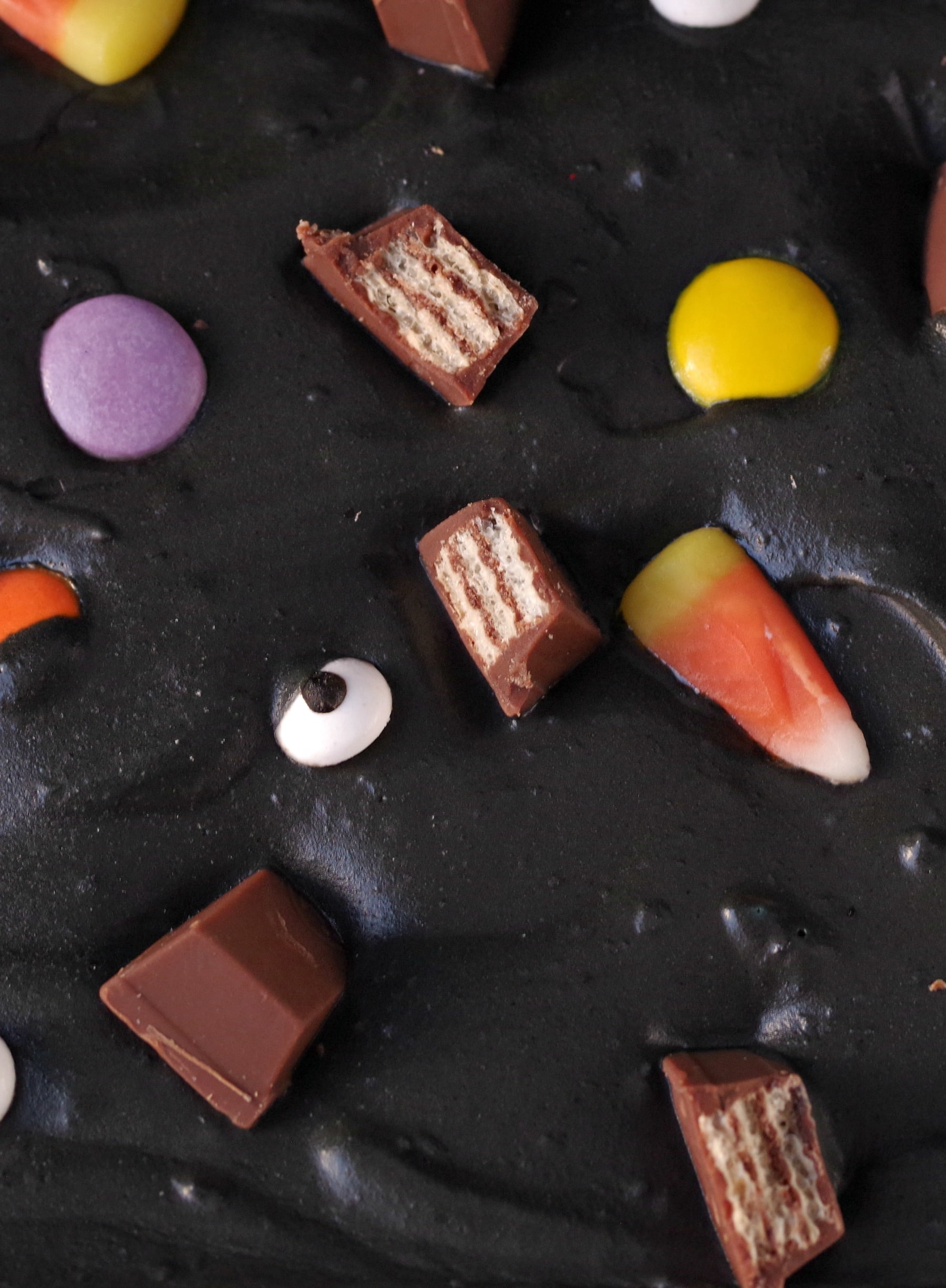 Boo Batter ice cream close up. It's a black ice cream with candy eyes, candy corn, chocolate bars and smarties.