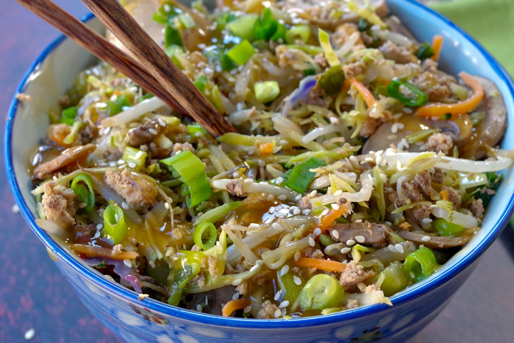 close up of egg roll in a blue bowl with chopsticks inside