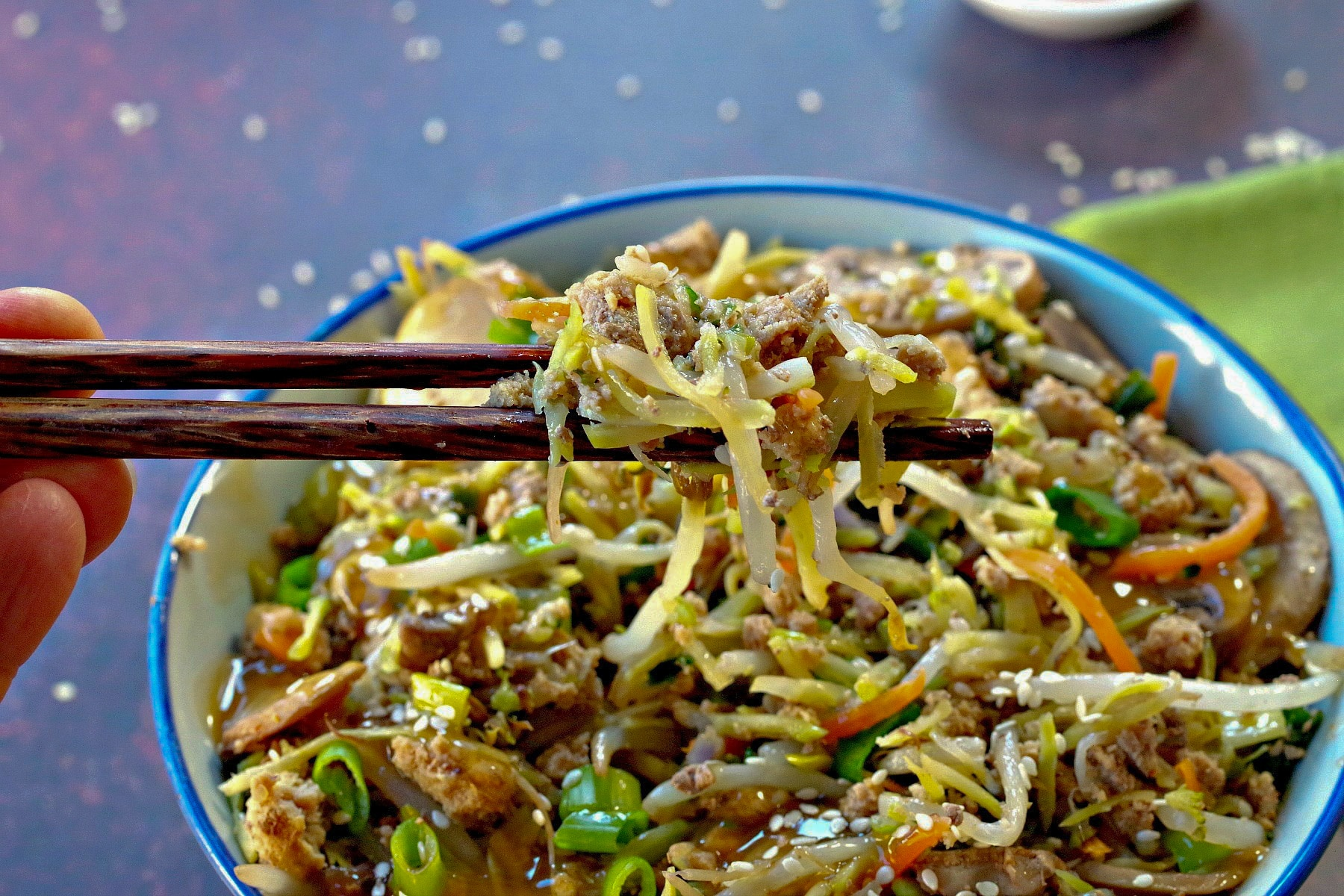 egg roll in a bowl in a blue bowl with some being held up with chopsticks