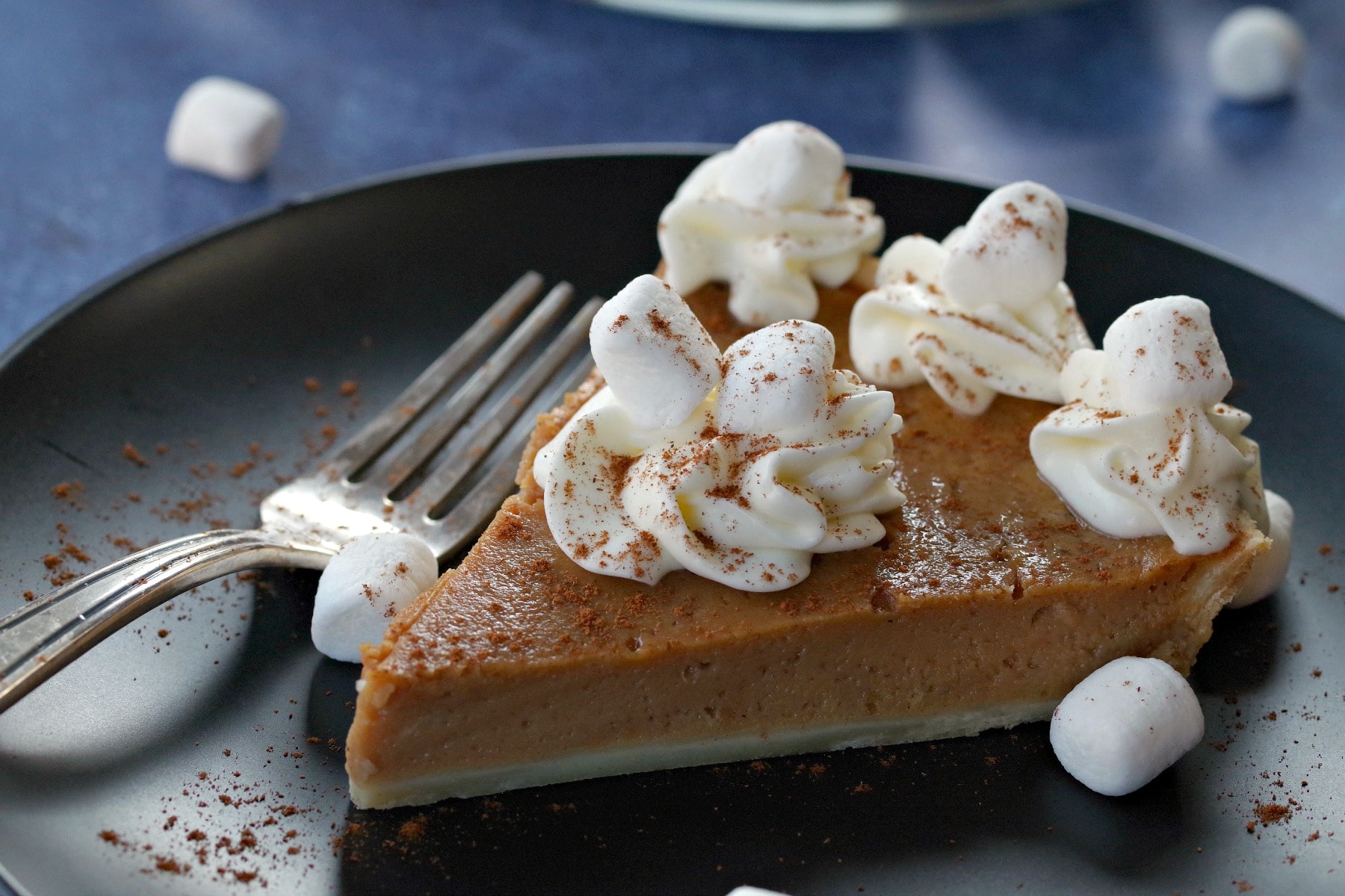 sweet potato pie on black plate on blue background with marshmallows around