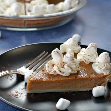 Piece of Sweet Potato Pie with Marshmallow Whipped Cream on Black plate on blue background with whole pie in glass pie plate in the background