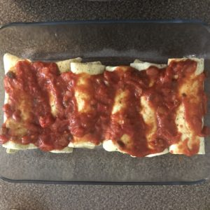 unbaked enchiladas in casserole dish with salsa on top
