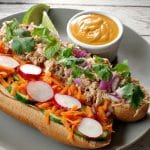open chicken banh mi vietnamese sub on a greenish grey plate with lime garnish and small white dish of sriracha mayonnaise