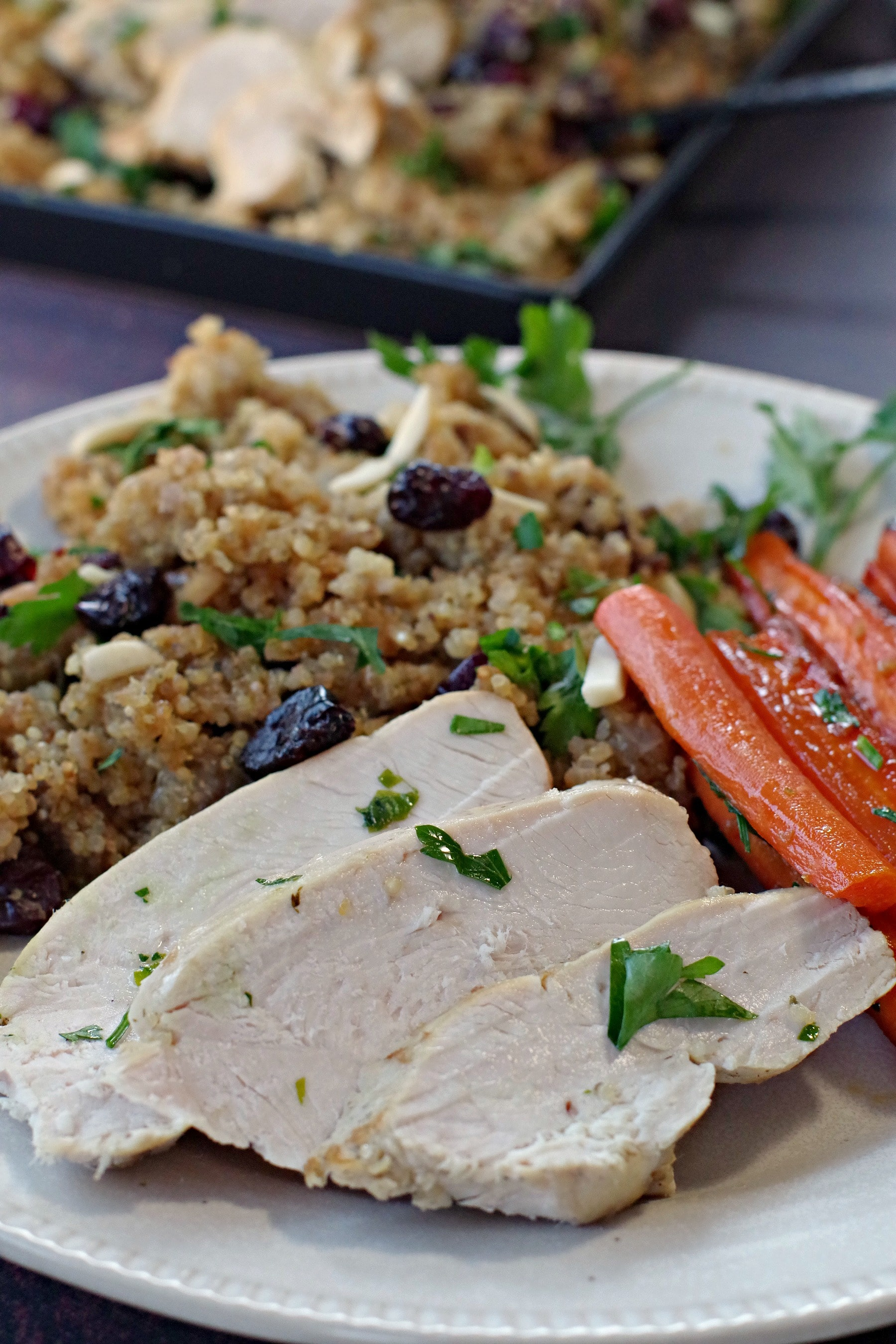 key breast with Cranberry Quinoa Dressing and roasted, glazed carrots on a beige dinner plate and black tray of turkey and dressing in the background