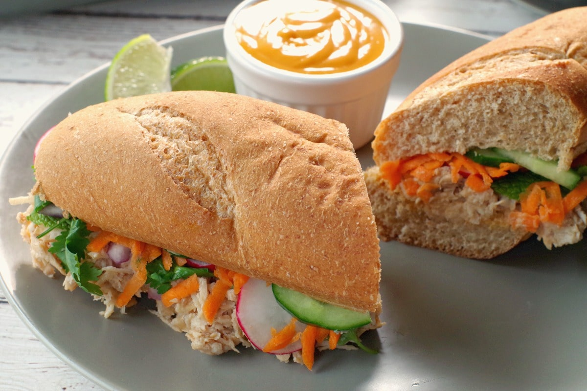 Chicken Vietnamese sub, sliced in half, with a small white dish of sriracha mayo and lime wedges on a greenish-grey plate