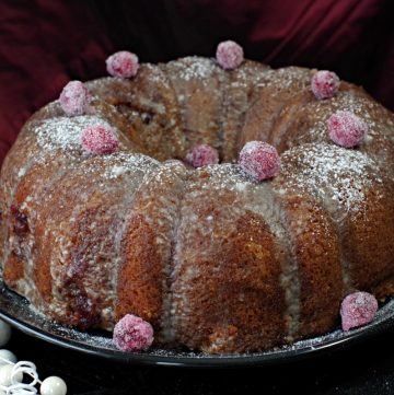 Cranberry coffee cake with coffee glaze and candied cranberries on a black platter