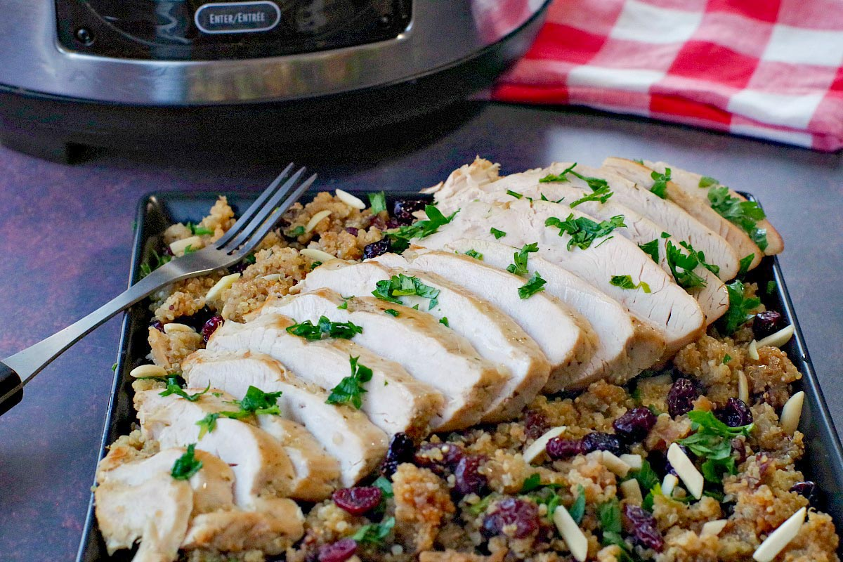 sliced slow cooker turkey breast on bed of cranberry quinoa dressing (on black platter) with slow cooker and checkered red tea towel in the background