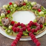gingerbread fruit wreath on a white cardboard cake platter on a brown faux wooden surface