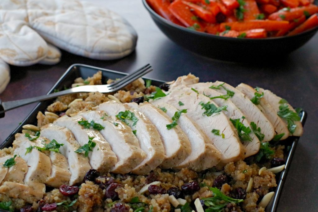 sliced slow cooker turkey breast on bed of cranberry quinoa dressing (on black platter) with black bowl of roasted carrots and festive oven mitts in the background