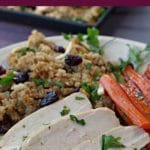 Pinterest pin with text on the top and bottom and photo of turkey breast with Cranberry Quinoa Dressing and roasted, glazed carrots on a beige dinner plate and black tray of turkey and dressing in the background
