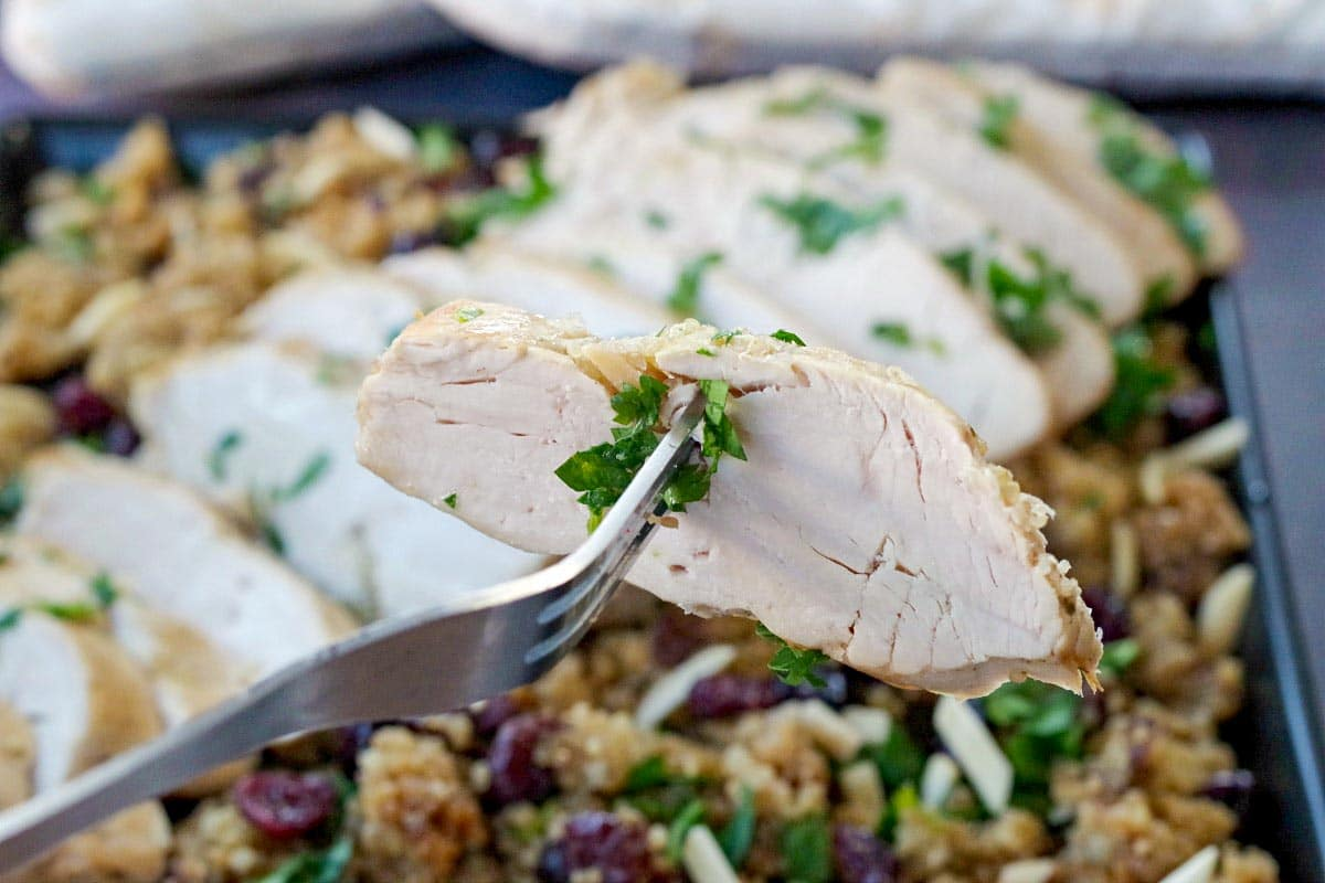 Piece of turkey breast being held up on a fork, over a platter of sliced turkey breast on cranberry quinoa dressing