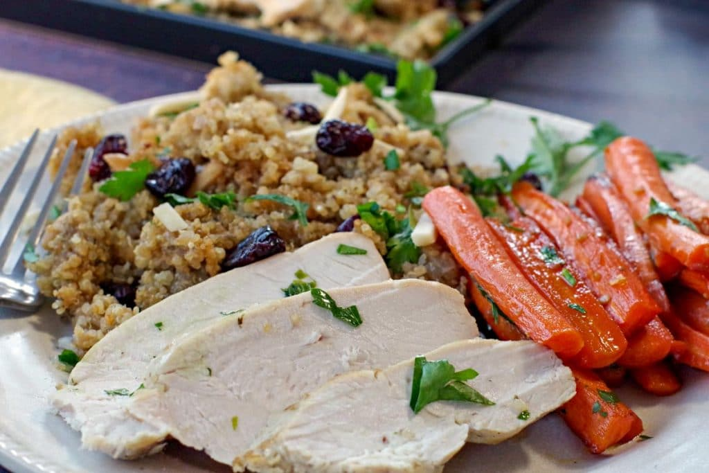 slices of slow cooker boneless turkey breast on a white plate with glazed carrots and quinoa dressing