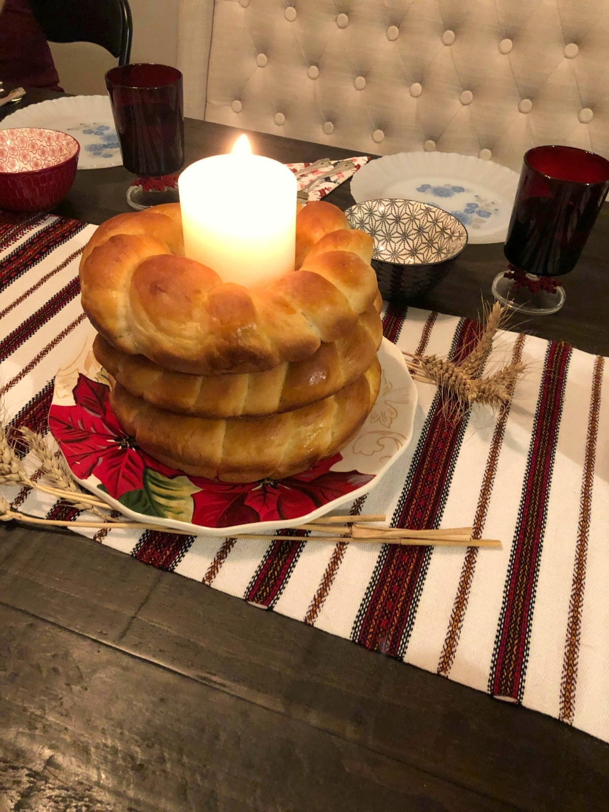 3 Kolach stacked, with a candle in the middle on a table with dinner plates and a striped red and white table runner