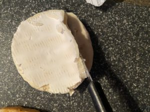 rind being sliced off brie cheese