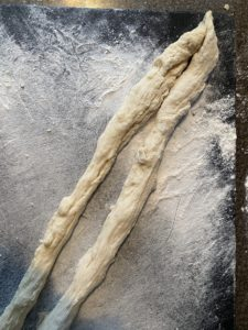2 pieces of kolach shaped into 2 - 28 inch long pieces on floured cutting board