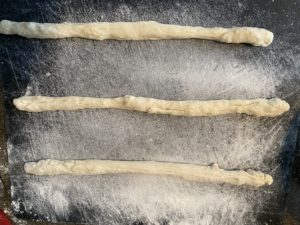3 pieces of dough on floured cutting board