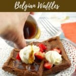 Pinterest pin with text at the top and bottom and a photo of chocolate belgian waffles with syrup being poured over them