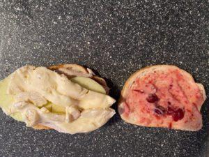 one slice of bread with fig spread, turkey, apples and brie and other other slice of bread with cranberry aioli