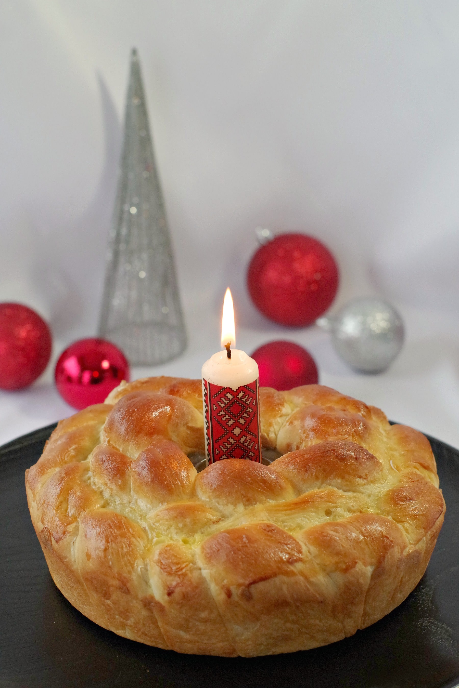 Kolach Ukrainian Christmas Bread on black platter with Ukrainian candle in the middle and Christmas decorations in the backgro