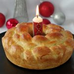 Kolach Ukrainian Christmas Bread on black platter with Ukrainian candle in the middle and Christmas decorations in the background