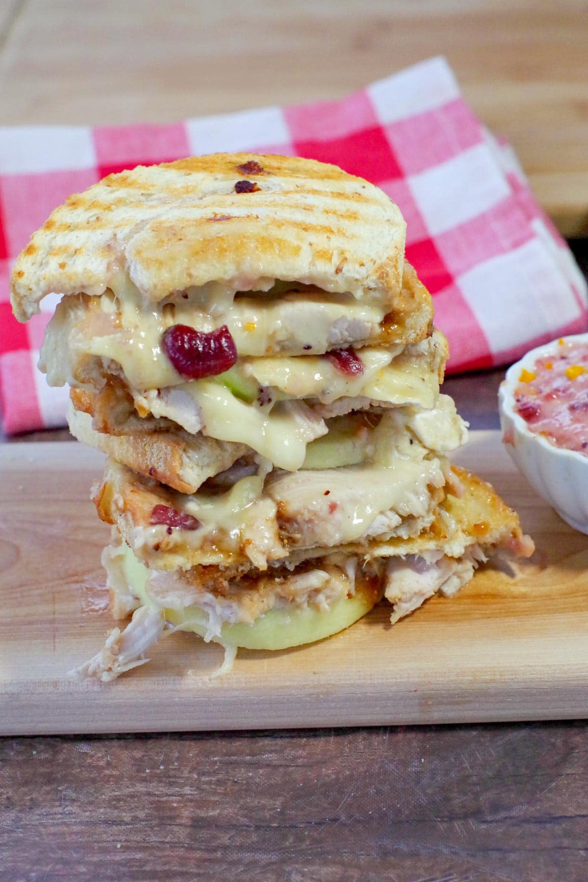 Leftover Turkey Panini stacked on a cutting board, with red checkered tea towel in the background