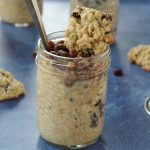 raisin cookie oatmeal in a jar with cookie on top on blue background with raisin oatmeal cookies around