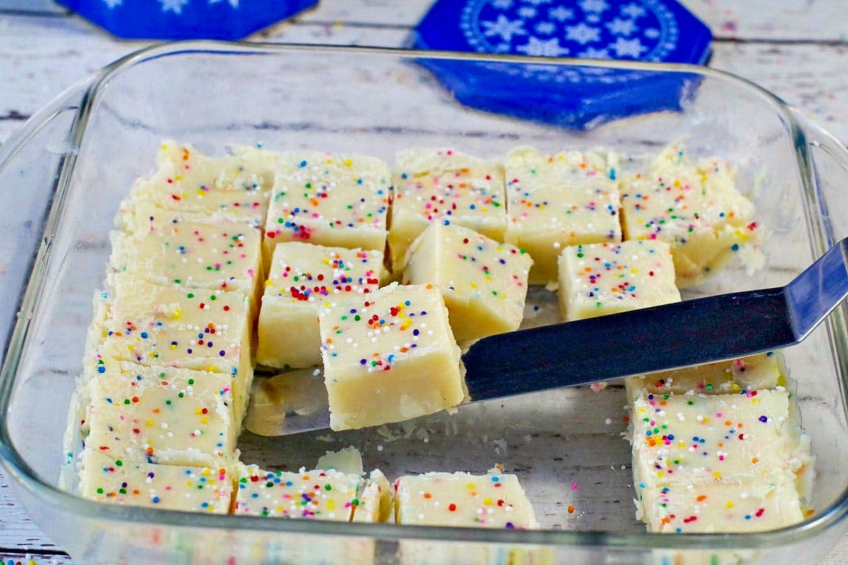 squares of sugar cookie fudge in a glass container with a spatula lifting on out
