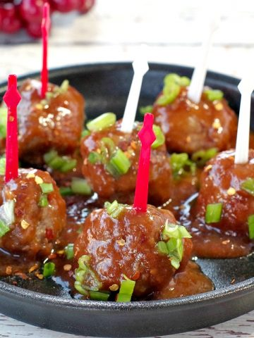 6 slow cooker turkey meatballs with red and white skewers on a black, round serving platter