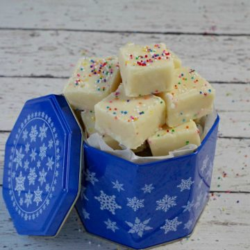 microwave sugar cookie fudge in a tall blue tin (with white snowflake pattern) on a white wooden surface