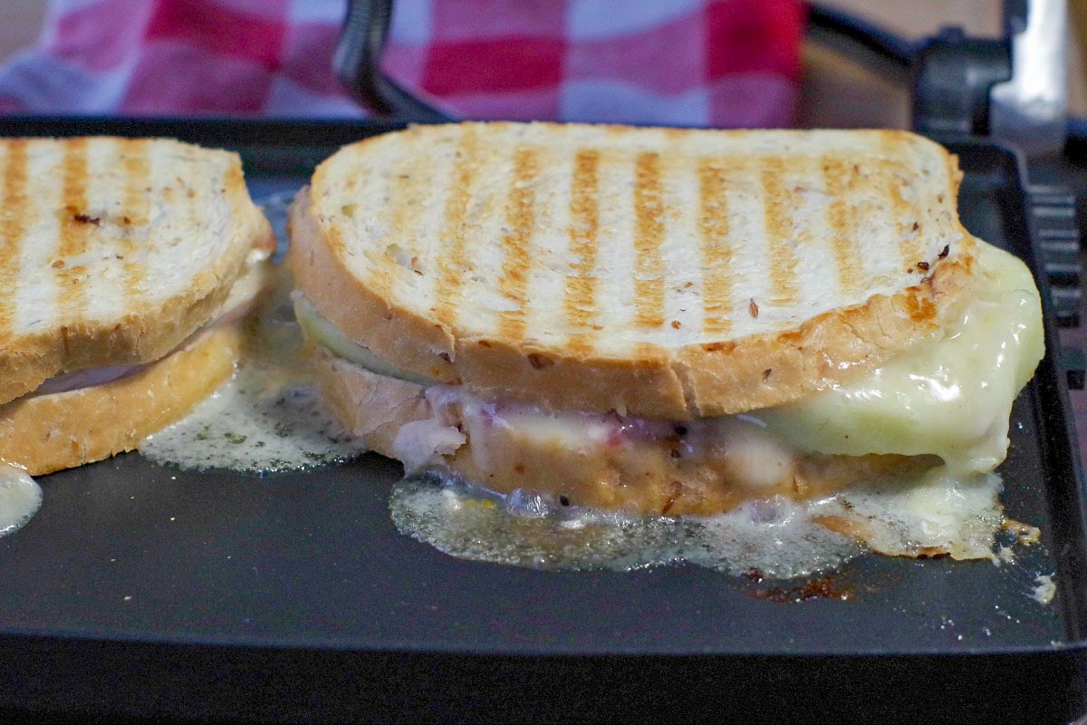 Turkey Brie Cranberry Sandwich cooking on a Panini press