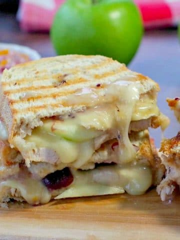 Turkey Panini with cranberry and brie on a cutting board with green apples and cranberry aioli in the background