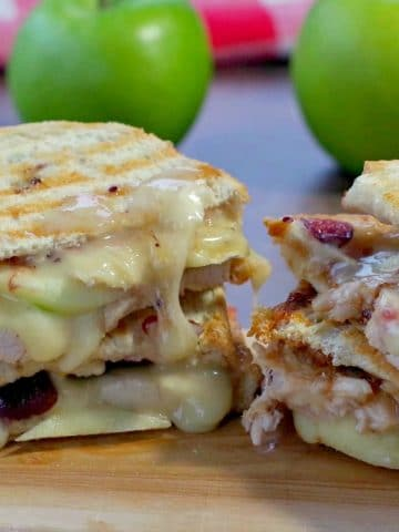 turkey and cranberry panini on cutting board with green apples and cranberry aioli in background