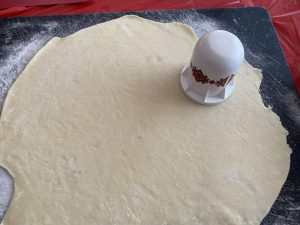 perogy dough rolled out with cutter on top
