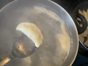 perogy being removed from boiling water with slotted spoon (after floating to the top)