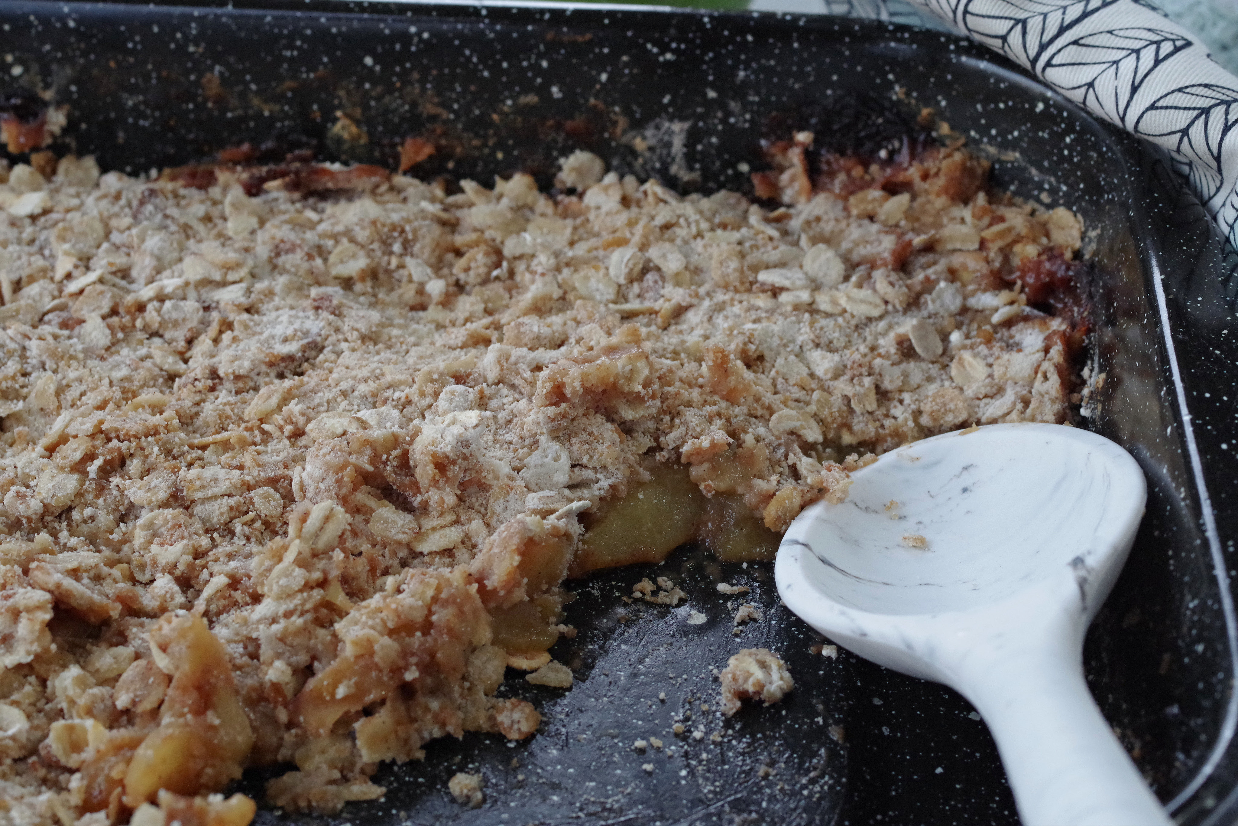 pan of weight watchers apple crisp with oatmeal in a dark blue pan with a white spoon