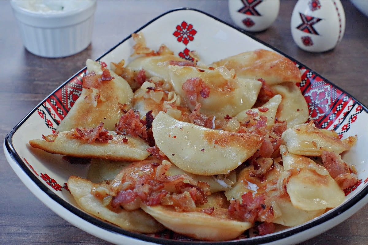 Ukrainian perogies covered in bacon and onion in a ukrainian print dish