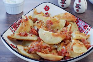 cottage cheese perogies with bacon and onion on a Ukrainian plate, on brown faux wooden surface