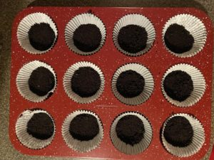 Oreo cookie baking crumb mixture pressed into muffin liner in muffin tin