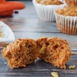 carrot muffin on blue wood-like surface, pulled into 2 pieces , with wrapper, more muffins and carrots in background
